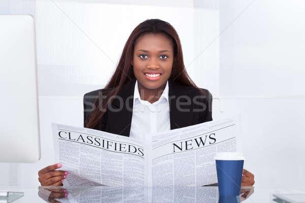 Businesswoman Reading Newspaper At Desk Stock photo © AndreyPopov