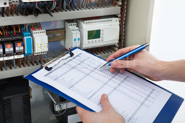Electrician Holding Clipboard While Examining Fusebox Stock photo © AndreyPopov