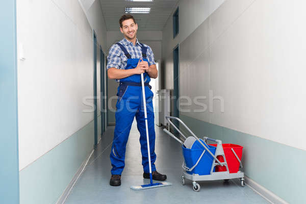 Happy Male Worker With Broom Cleaning Office Corridor Stock photo © AndreyPopov