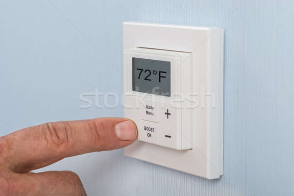 Person Adjusting Temperature Of Thermostat Stock photo © AndreyPopov