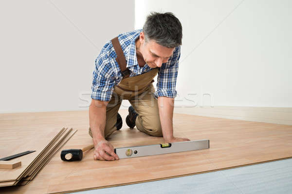 Man Installing New Laminated Wooden Floor Stock photo © AndreyPopov