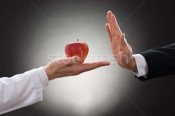 Person Refusing Apple Held By Doctor Stock photo © AndreyPopov