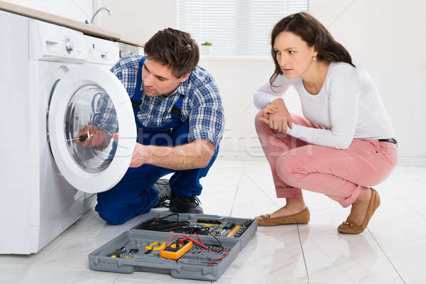 Repairman Repairing Washer In Front Of Woman Stock photo © AndreyPopov