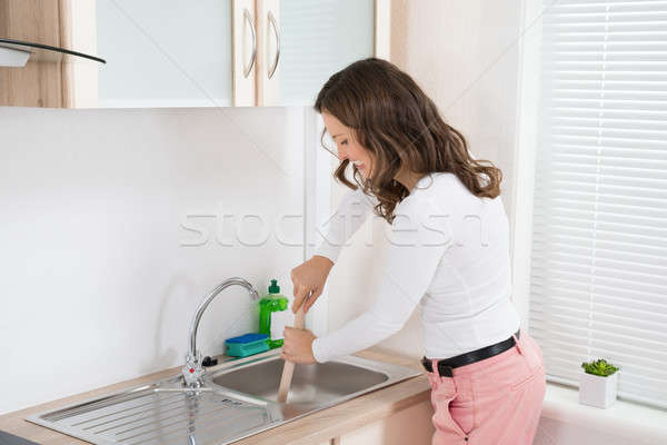 Woman Using Plunger In Sink Stock photo © AndreyPopov