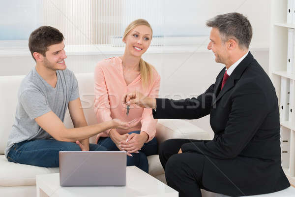 Real Estate Agent Giving House Key To Couple Stock photo © AndreyPopov