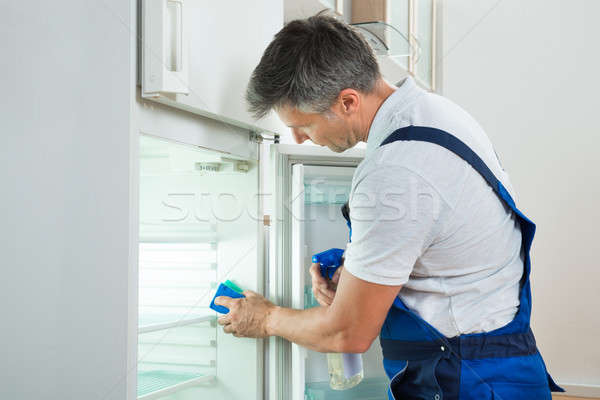 Janitor Cleaning Refrigerator At Home Stock photo © AndreyPopov