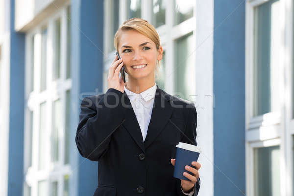 Businesswoman Using Mobile Phone During Lunch Break Stock photo © AndreyPopov