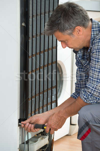 Serviceman Working On Fridge At Home Stock photo © AndreyPopov