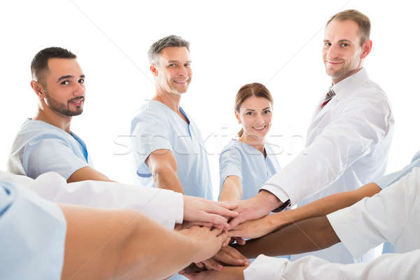 Portrait Of Smiling Medical Team Piling Hands Stock photo © AndreyPopov