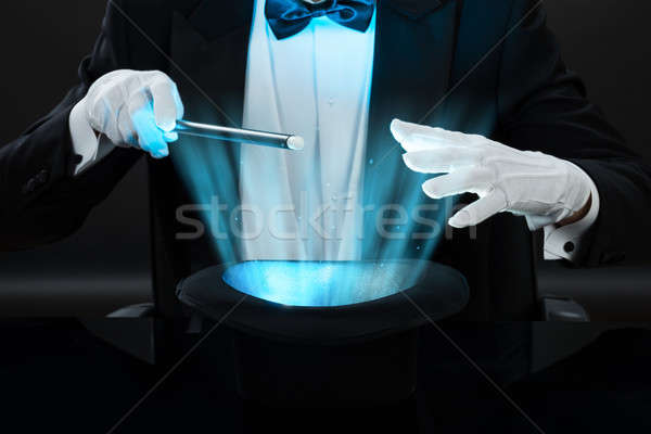 Magician Holding Magic Wand Over Illuminated Hat Stock photo © AndreyPopov