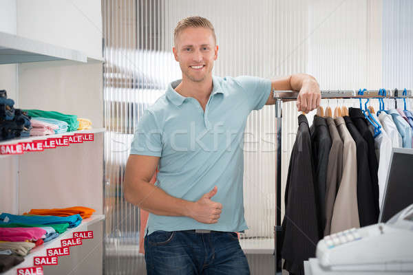 Confident Salesman Leaning On Rack In Clothing Store Stock photo © AndreyPopov