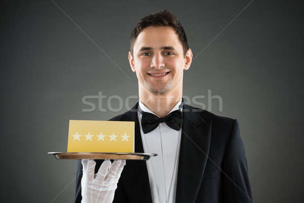 Happy Waiter Holding Tray With Star Rating Label Stock photo © AndreyPopov