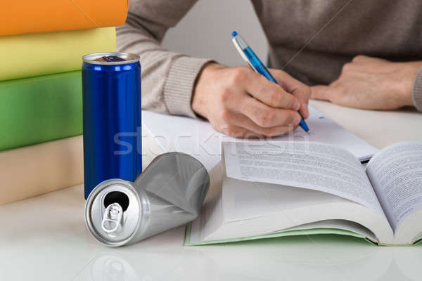 Male Student Writing In Book At Table Stock photo © AndreyPopov
