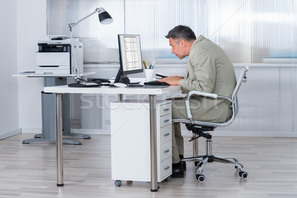 Concentrated Businessman Using Computer At Desk Stock photo © AndreyPopov