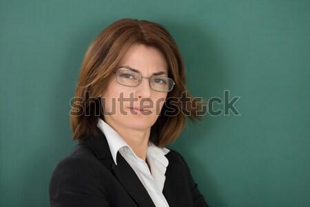 Female Teacher Standing Against Green Chalkboard Stock photo © AndreyPopov