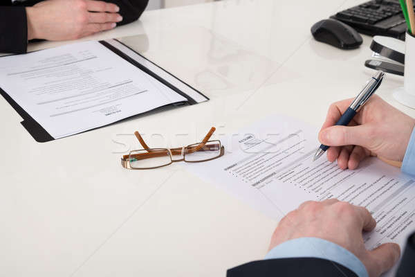 Businessperson Holding Pen Over Resume Stock photo © AndreyPopov