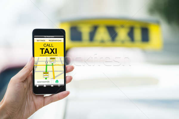 Female's Hand Holding Mobile Phone Booking Taxi Stock photo © AndreyPopov