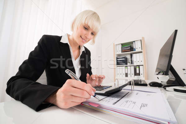 Businesswoman Calculating Invoice In Office Stock photo © AndreyPopov