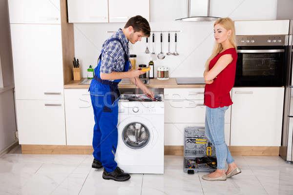 Mężczyzna pracownika pralka kuchnia młoda kobieta Zdjęcia stock © AndreyPopov