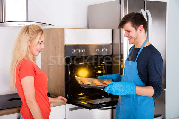 Young Happy Couple Preparing Cookies In Kitchen Stock photo © AndreyPopov