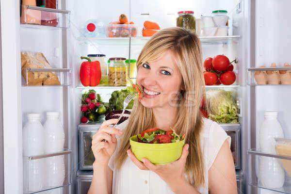 Mujer comer ensalada refrigerador jóvenes feliz Foto stock © AndreyPopov