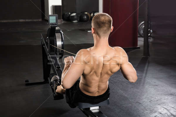 Man Working Out On Row Machine Stock photo © AndreyPopov