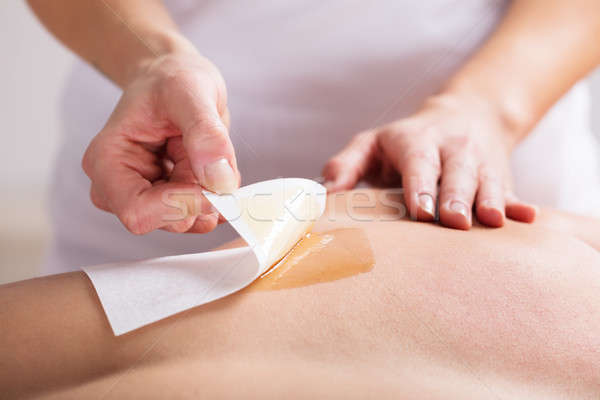 Woman Waxing Man's Chest With Wax Strip Stock photo © AndreyPopov