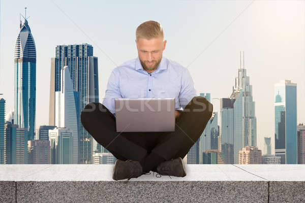 Man Sitting On The Rooftop Using Laptop Stock photo © AndreyPopov