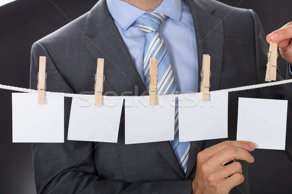 Businessman Pinning Blank Paper On Clothesline Stock photo © AndreyPopov