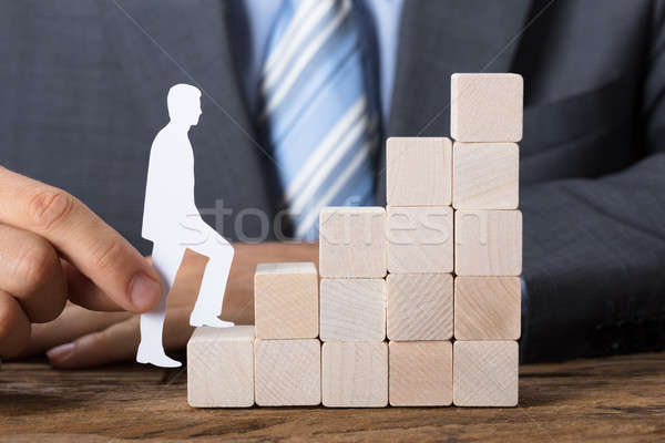 Businessman Moving Paper Man Upstairs Made Of Wooden Blocks Stock photo © AndreyPopov