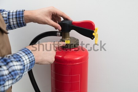 Technician's Hand Pointing To Symbol On Red Fire Extinguisher Stock photo © AndreyPopov