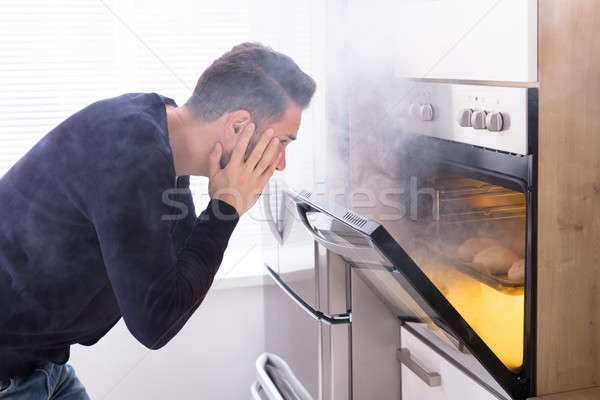 Shocked Man Looking At Burnt Cookies In Oven Stock photo © AndreyPopov
