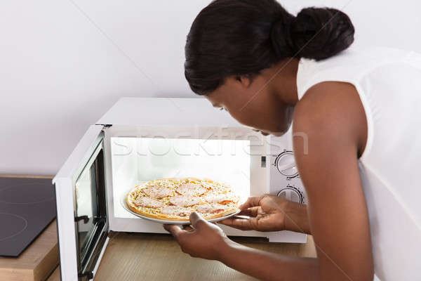 Woman Baking Pizza In Microwave Oven Stock photo © AndreyPopov