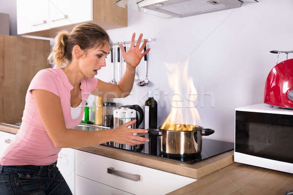 Shocked Young Woman Looking At Cooking Pot On Fire Stock photo © AndreyPopov