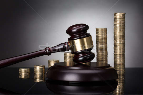 Gavel On Sounding Block In Front Of Stacked Coins Stock photo © AndreyPopov