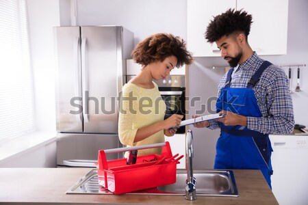 Woman Signing Invoice In Kitchen Stock photo © AndreyPopov