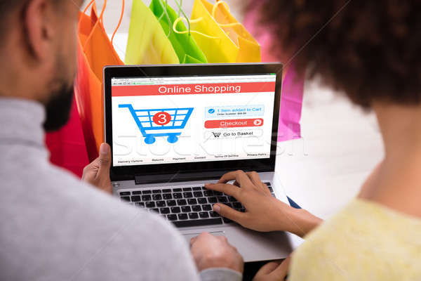 Stock photo: Couple Shopping Online In Front Of Multi Colored Shopping Bags