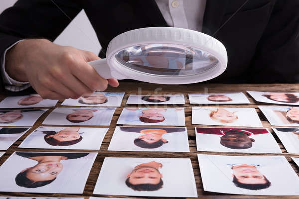 Looking At Candidate's Photograph With Magnifying Glass Stock photo © AndreyPopov