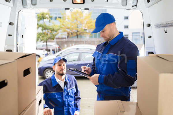 Mover Looking At His Partner Writing On Clipboard Stock photo © AndreyPopov