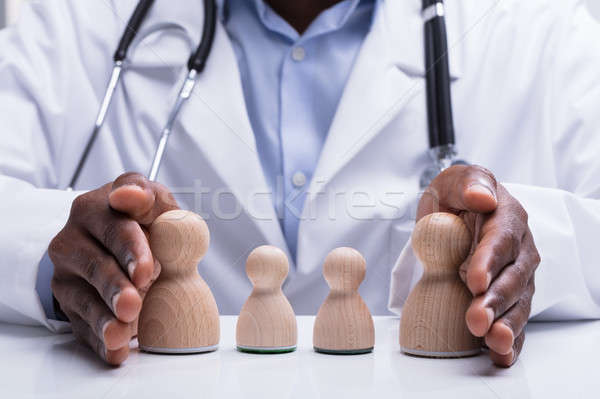 Doctor's Hand Protecting Wooden Pawn Family Stock photo © AndreyPopov