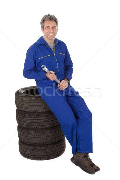 Automechanic sitting on car tires Stock photo © AndreyPopov