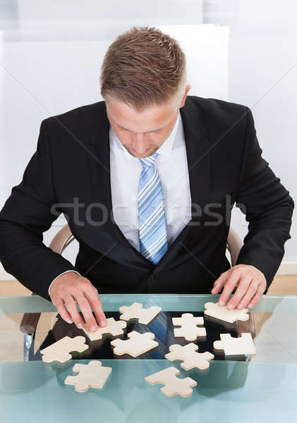 Businessman solving a jigsaw puzzle at his desk Stock photo © AndreyPopov