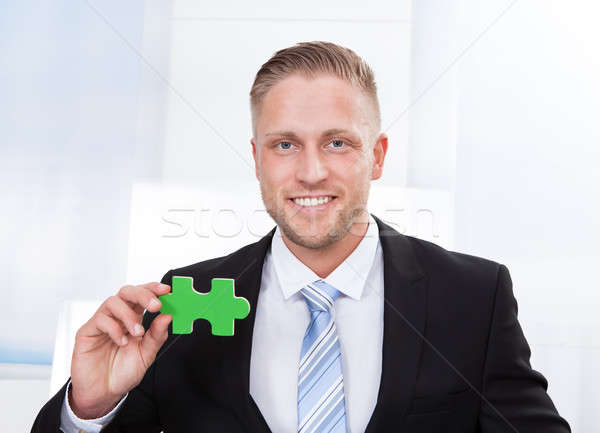 Successful businessman holding a puzzle piece Stock photo © AndreyPopov