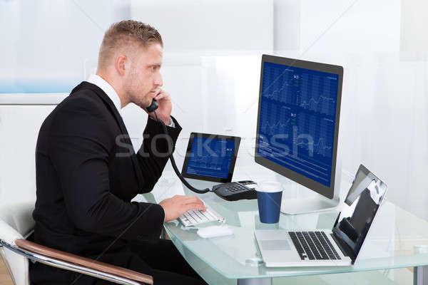 Hardworking businessman at his desk Stock photo © AndreyPopov