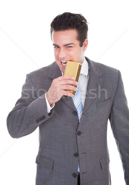 Businessman Biting Gold Bar Stock photo © AndreyPopov