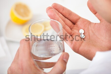 Man Taking Pills With Glass Of Water Stock photo © AndreyPopov