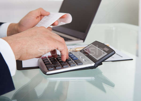 Businessman Calculating Expense In Office Stock photo © AndreyPopov