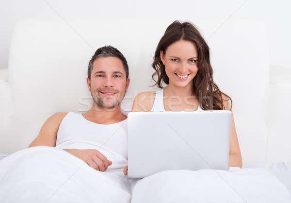 Stock fotó: Boldog · pár · laptopot · használ · portré · mosolyog · ágy
