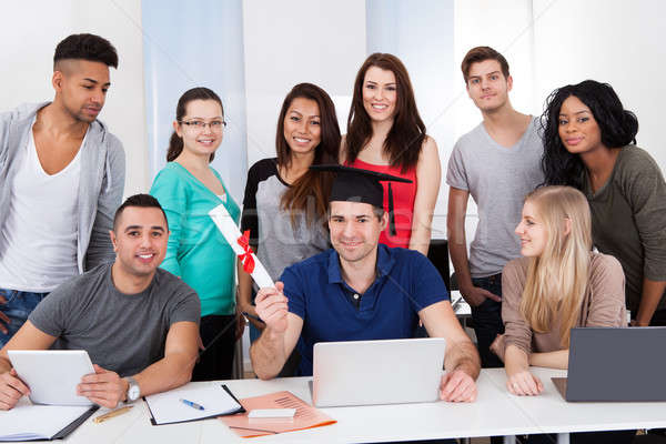 College Student Holding Degree With Classmates Looking At Him Stock photo © AndreyPopov