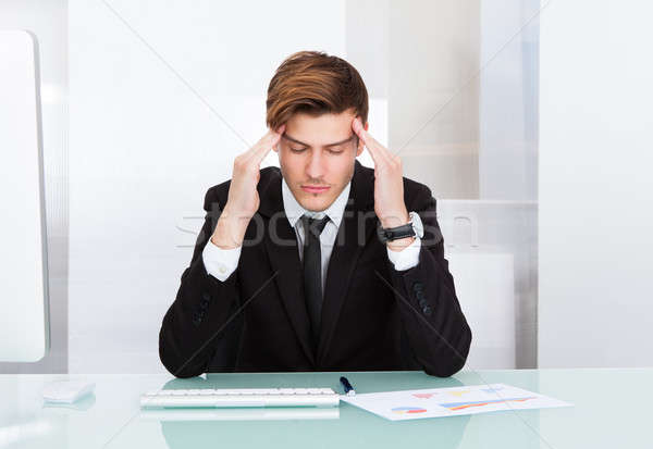 Stock photo: Young Businessman Suffering From Headache In Office